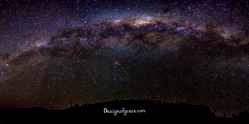 The blue and purple milky way above with the silhouette of the land below in Cosy Corner, Albany, Western Australia