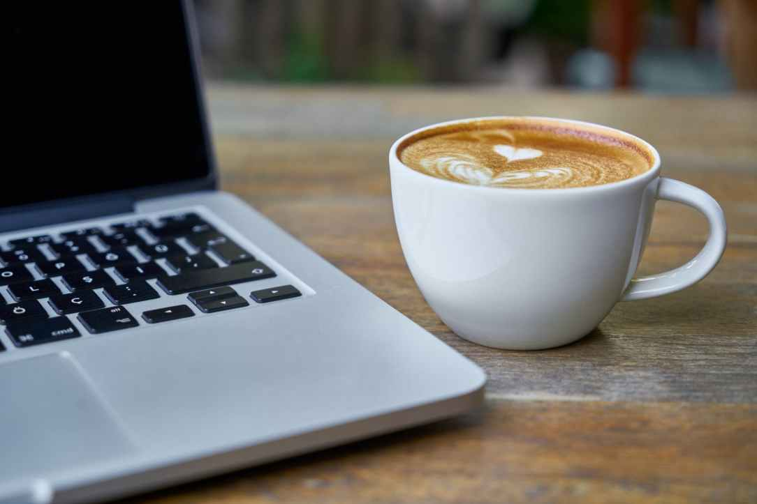 A laptop and a cup of coffee placed on a wooden table.  The coffee froth has a heart shape.