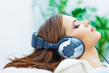 Young woman listening to binaural beats with closed-back headphones.