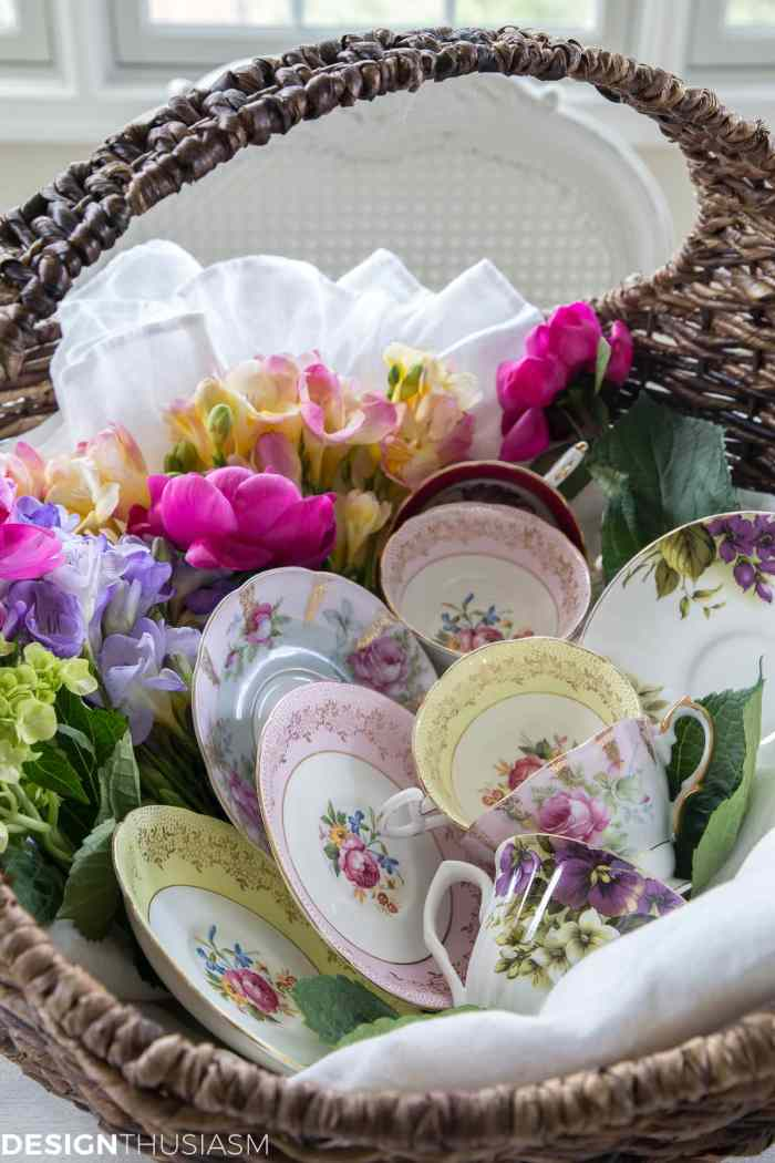 vintage teacups and saucers displayed in a basket with flowers