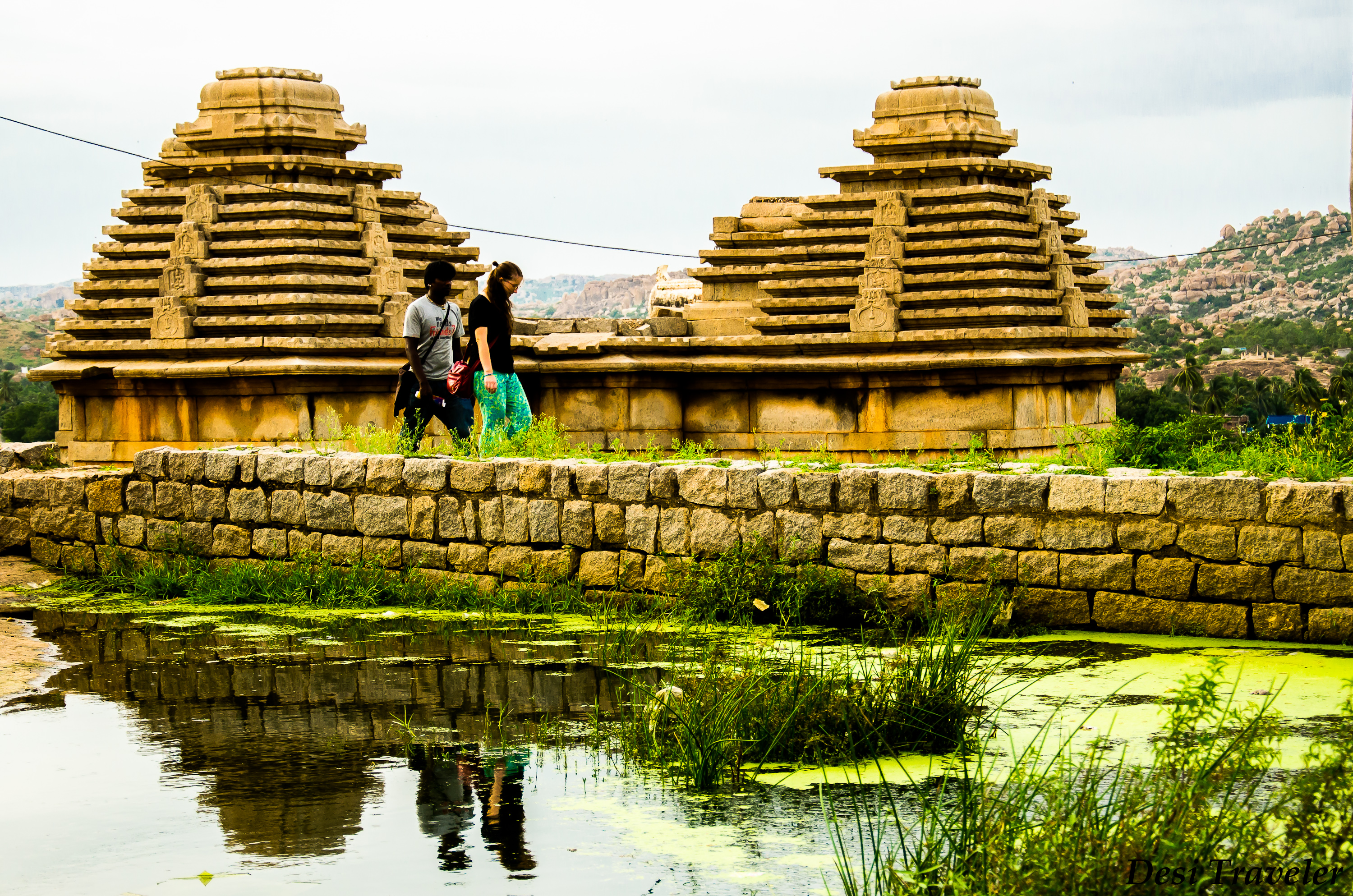 a backpacker and a guide in ruins of hampi
