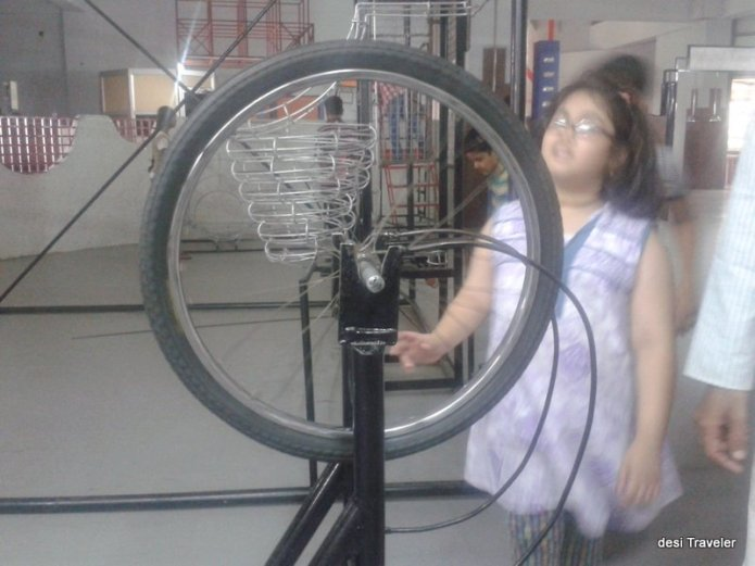 A girl checking a science exhibit at Birla Science Museum and Planetarium