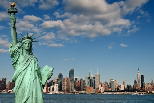 statue of liberty with her tablet with Manhattan in background