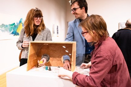"""Cole Pruitt and Rachel Kalman (left) interact with the exhibit he created with Lara Head titled """"Freedom of Assembly"""" while Sara Weininger looks on at the Parabola: Assembly exhibition, Des Lee Gallery, Washington University, St. Louis, MO"""