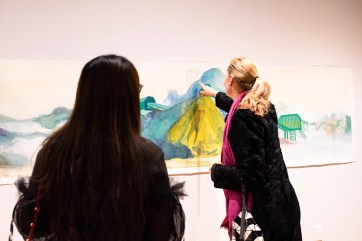 """Sixue Yang (left) talks with Patricia Olynyk, Director, Graduate School of Art, Sam Fox School of Design & Visual Arts, about her piece """"Fusing"""" at the Parabola: Assembly exhibition, Des Lee Gallery, Washington University, St. Louis, MO"""