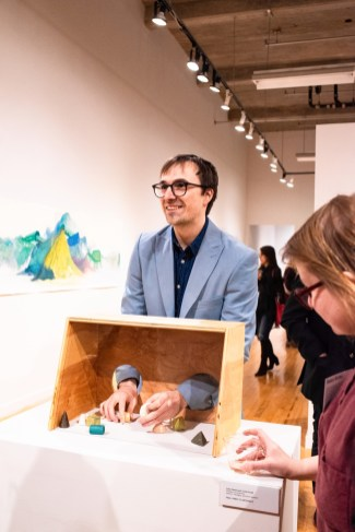 """Cole Pruitt interacts with the exhibit he created with Lara Head titled """"Freedom of Assembly"""" at the Parabola: Assembly exhibition, Des Lee Gallery, Washington University, St. Louis, MO"""