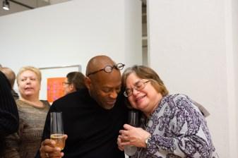 John Rhine (left) hugs Regina Dinam at the Robert C. Smith Retrospective Exhibit Opening, Des Lee Gallery, St. Louis, MO