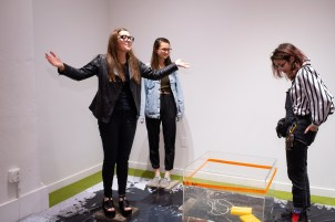 """from left, Libby Evan, Alessandra Ferrari-Wong, and Zoe Finkelstein interact with""""30minutes"""" by Megan Jiyoung Lee at the BFA 2 Show on display at the Des Lee Gallery, Washington University, St. Louis, MO"""