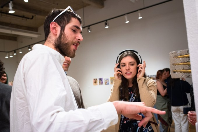 """Antonio Leone (left) listens to the piece """".50 Caliber Coat Check"""" by Merry Sun while Robert and Samantha Orf look on, BFA Show 2, Des Lee Gallery, Washington University, St. Louis, MO"""