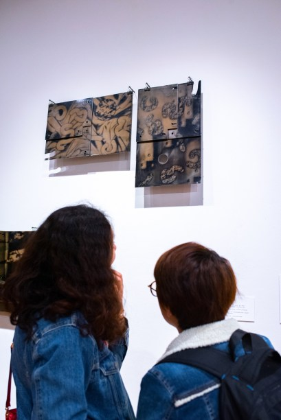 """Danning Liang (r) and Suyin Yao (l) view work at the Opening reception of the """"Decoys and Depictions: Images of the Digital"""" Exhibition at the Des Lee Gallery, Washington University, St. Louis, MO"""
