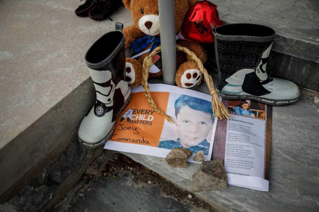 Una foto de Joey Commanda, un niño que murió mientras huía del Instituto Mohawk, se encuentra en un memorial improvisado en los escalones del antiguo internado en Brantford, Ontario.