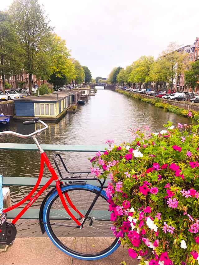 Bike e canal de Amsterdam cheio de flores