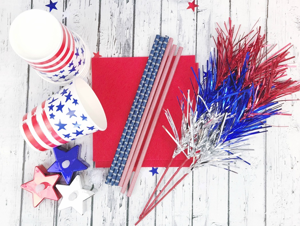 Supplies needed to make patriotic flameless torches including paper cups, paper straws, and patriotic themed candles.