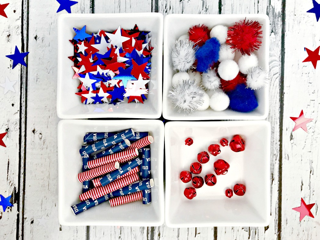 More supplies for the DIY paper straw necklaces includes stars, straws, pom poms, and jingle bells.