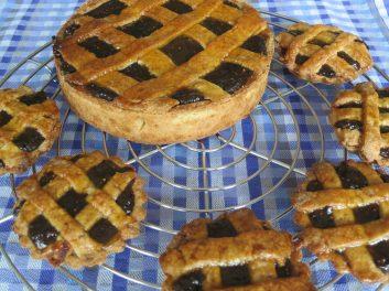 Grote en kleine pruimentaartjes op taartrooster