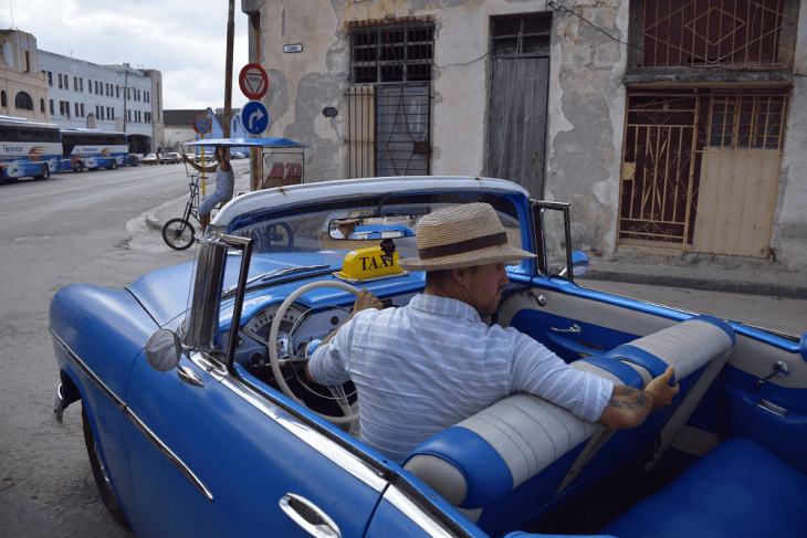 A taxi driver works the streets in a vintage car