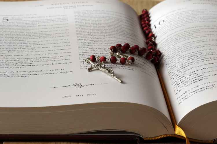 rosary on top of opened bible book