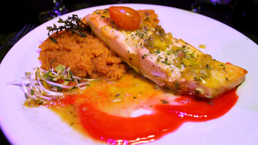 Salmón patagónico asado con puré de zapallo, servido en Madero Tango