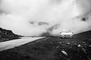 Small clean silver car parked on the side of the road with smoke and steam