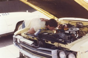 Old photo of a man cleaning a car engine at Rainbow Carwash Detail Plus in Sunnyvale, California