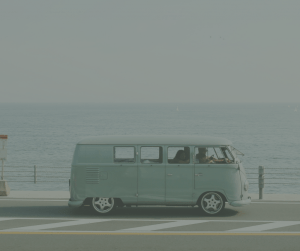 Light blue van on a road in front of the ocean
