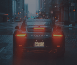 Black porsche with Texas plates on a cobblestone road with brake lights on