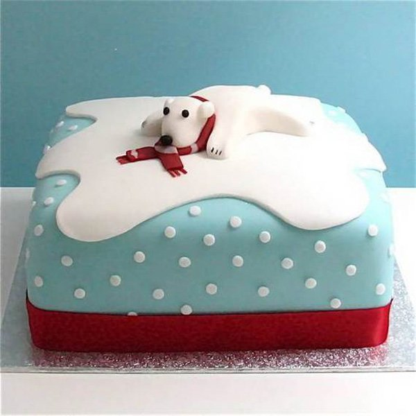Polar bear inspired Christmas cake. The cake looks like the snowy terrains of the north pole as the polar bear is happily sliding around on the white cold snow.