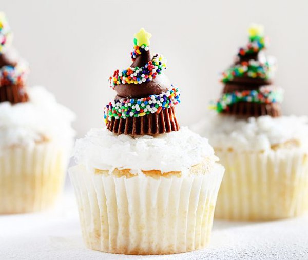 Christmas tree inspired Christmas cupcakes. The vanilla cupcakes are topped with chocolate toppings formed to look like Christmas trees surrounded by colorful candy sprinkles.