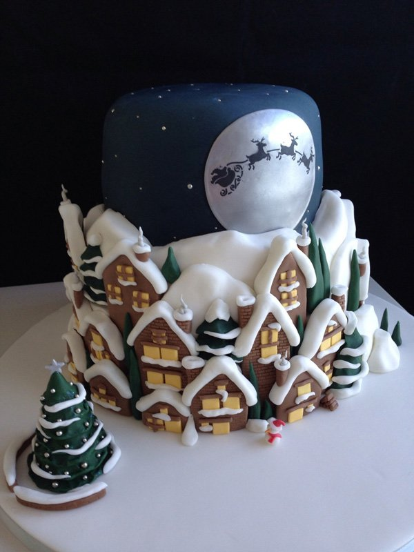 Christmas town inspired Christmas cake. The three layer cake is designed to look like a typical Christmas town at night filled with snow. In the skies you can see the silhouette of Santa riding the sleigh with his reindeer.