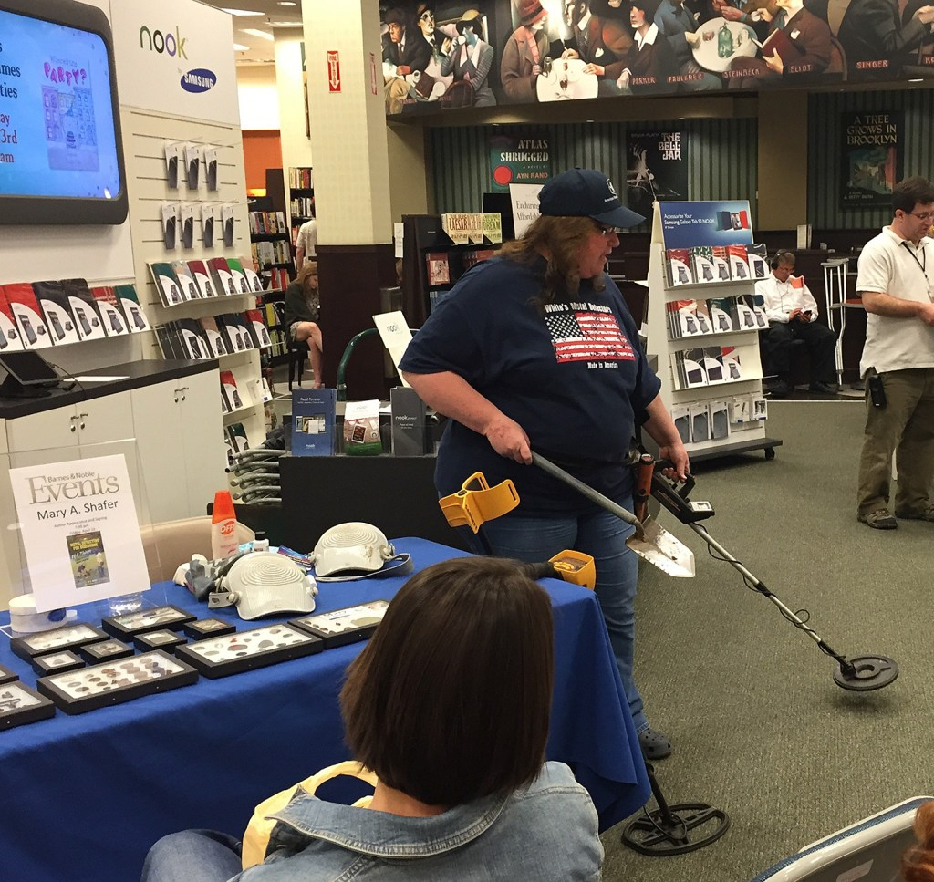 Author Mary Shafer demonstrates how to use a metal detector at an event at Barnes & Noble bookstore.