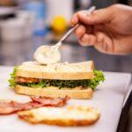 Pon mayonesa en ambos pedazos de pan, raros
