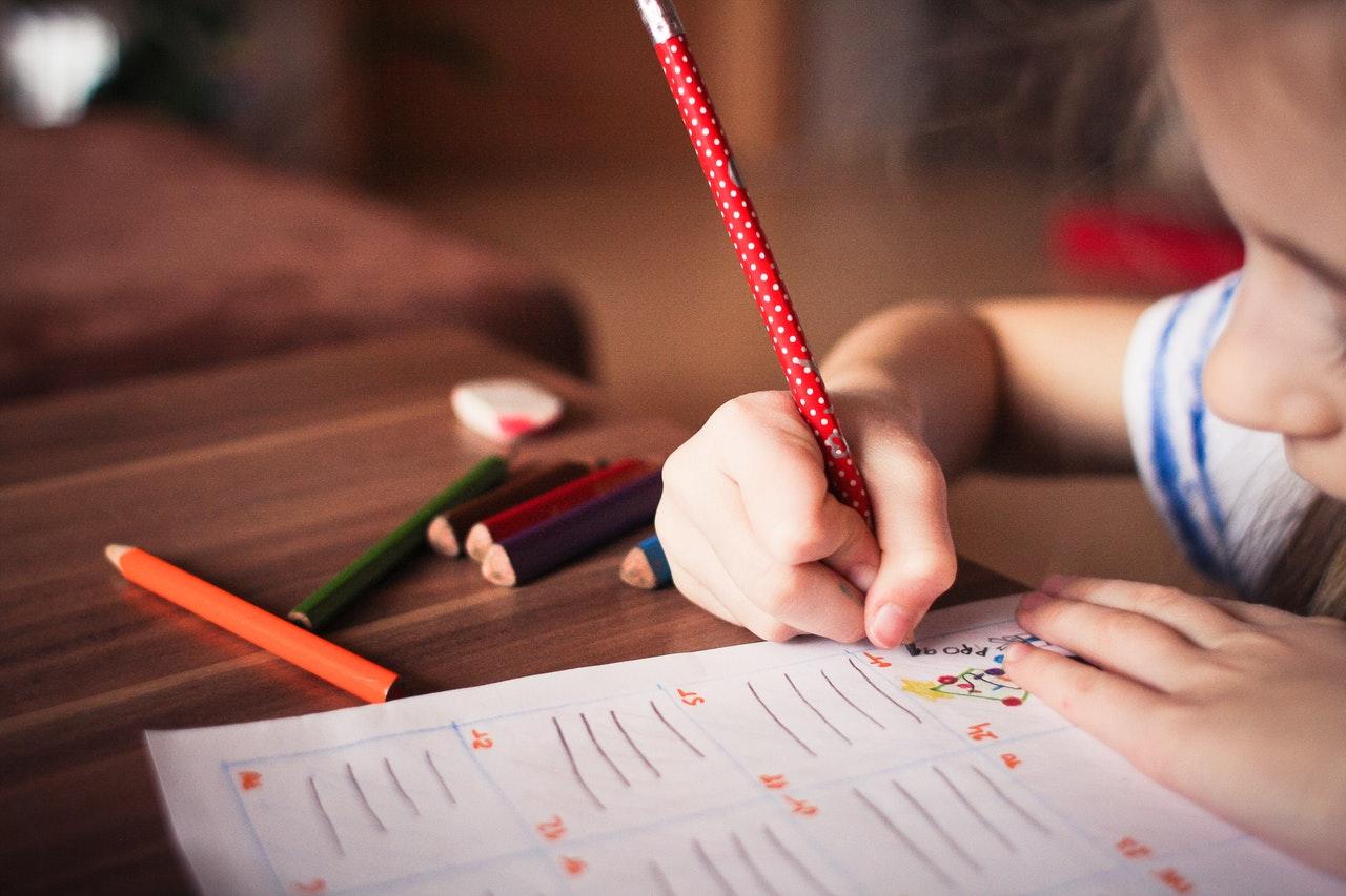 Kind aan schooltafel werkt in schoolschrift.