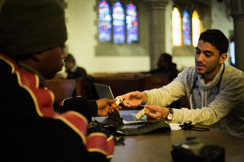 Street Medicine Detroit volunteer meets with patient at church