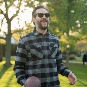 MuskOx, man wearing a green and black MuskOx flannel, black sunglasses, and holding a football