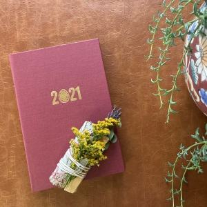 Naturally Empowered, flat lay of 2021 planner with a bundle of flowers and sage on top of it