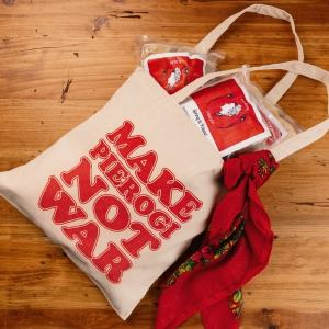 """Pietrzyk Pierogi, flat lay of canvas bag that says """"make pierogi not war"""" and packages of pierogi spilling out of the bag."""