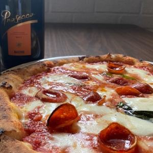 PizzaPlex, close up of a pepperoni pizza with a bottle of prosecco in the background