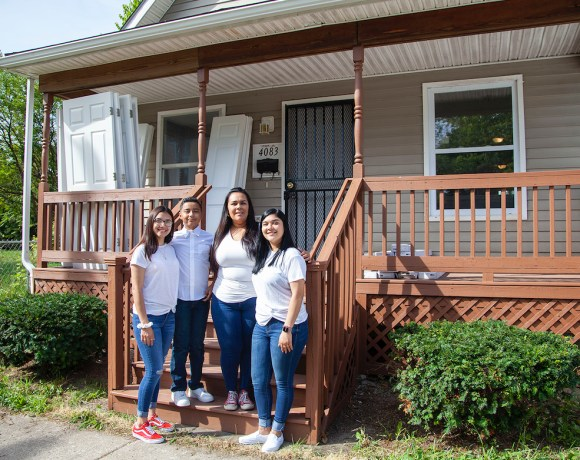 Diana Alaniz and her three children stand in front of their recently purchased house at the Newberry Homes in Detroit, through a Southwest Solutions program
