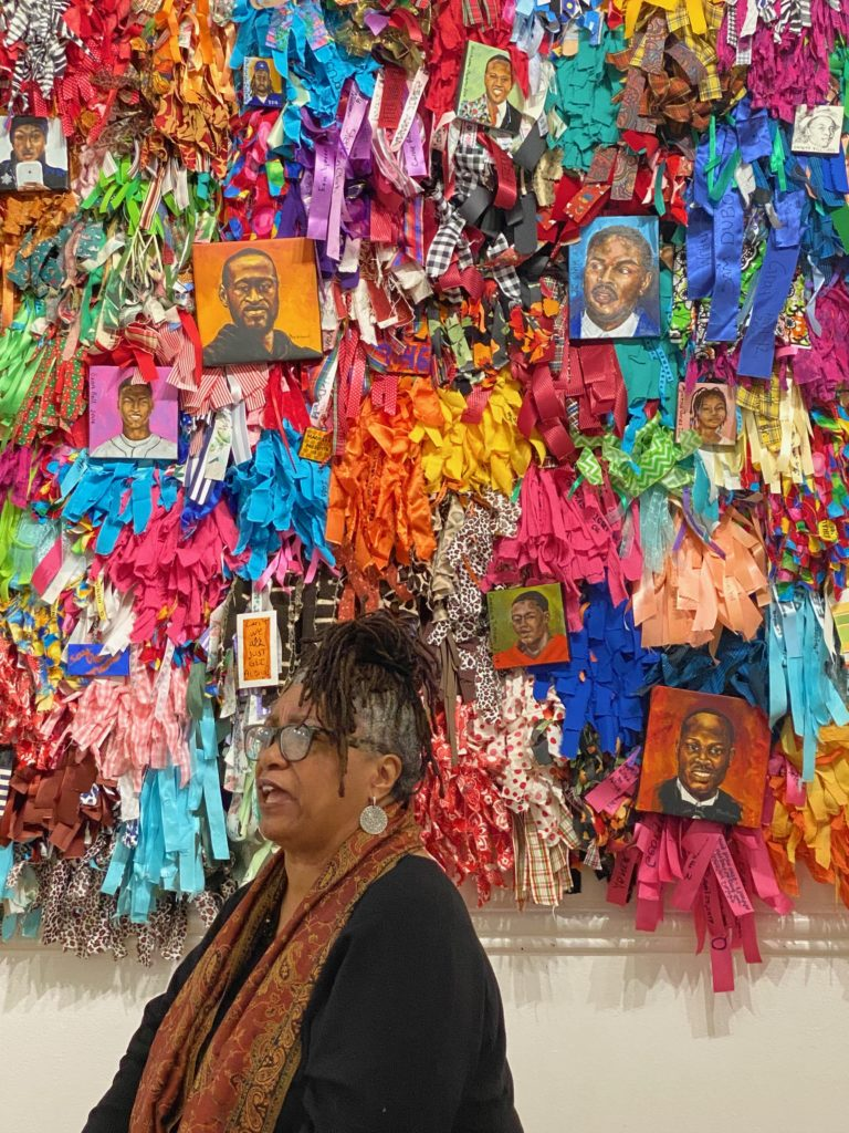 Carole Morisseau is standing in front of her artwork, The Healing Wall, at the Scarab Club in Detroit. In it, thousands of colorful ribbons honor victims of police brutality.