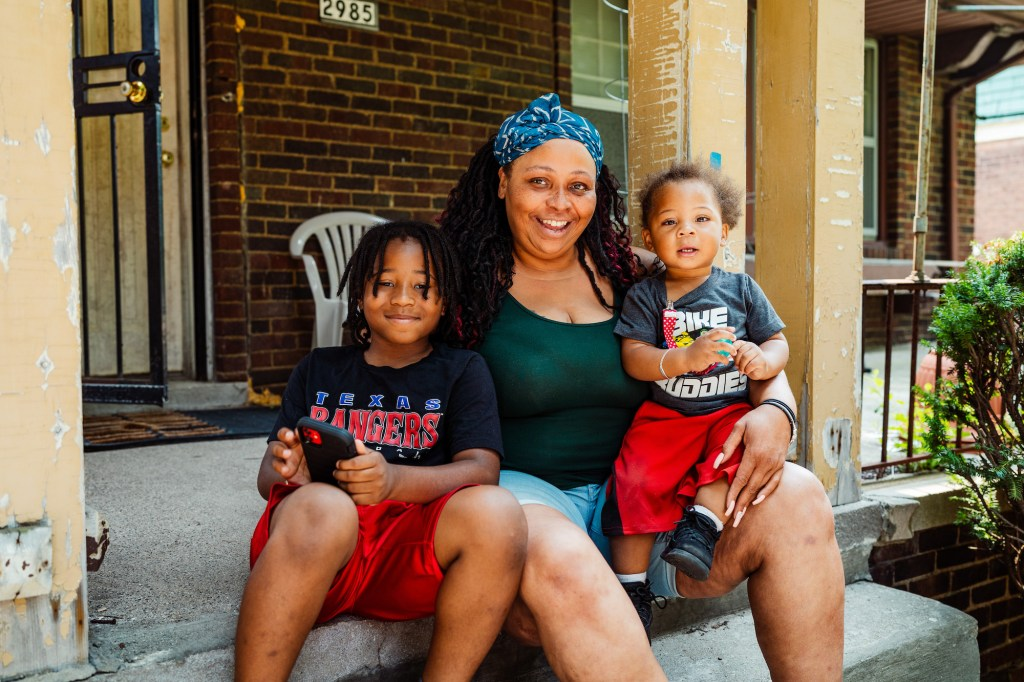 From left, Lloyd Toliver, 9, TaNiccia Henry and Ean Toliver, 1, on their front porch. Credit: Nick Hagen