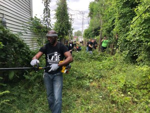 Volunteers work to clean up an alley near the Durfee Innovation Society.
