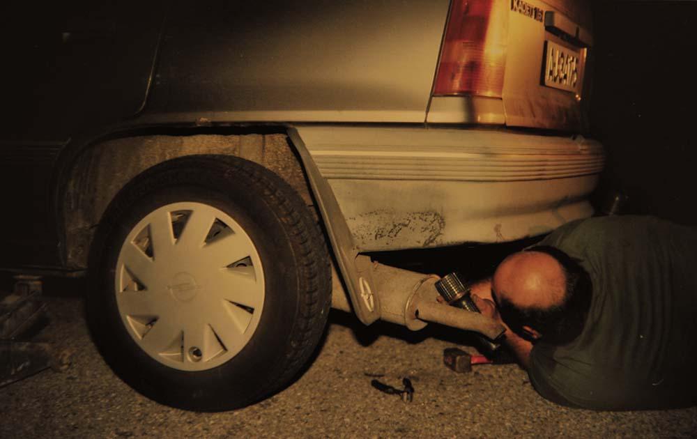 Mann fester eksosanlegget på en Opel Kadett