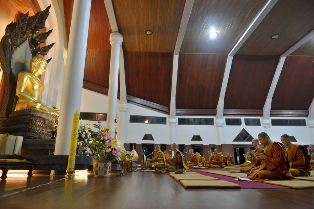 Buddhistmunker mediterer i kloster i Thailand