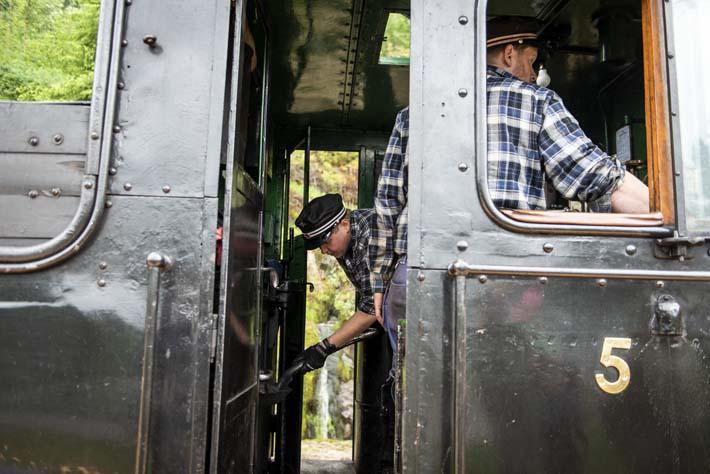 Fyrbøteren kaster på kull i ovnen på damplokomotivet på Setesdalsbanen