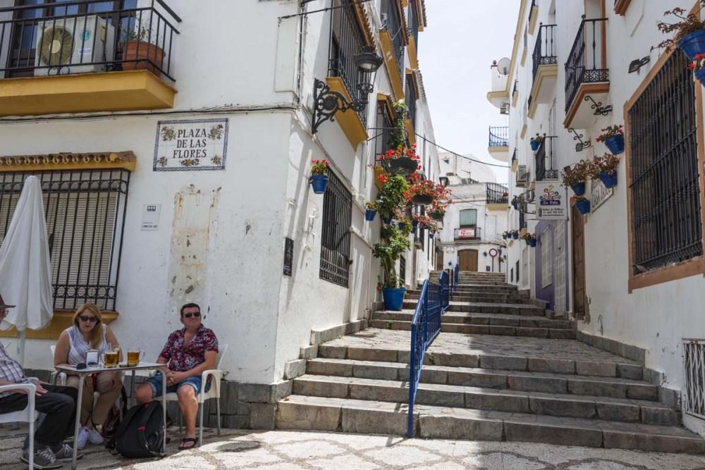 Folk sitter ved en bar i Plaza de las Flores i Estepona