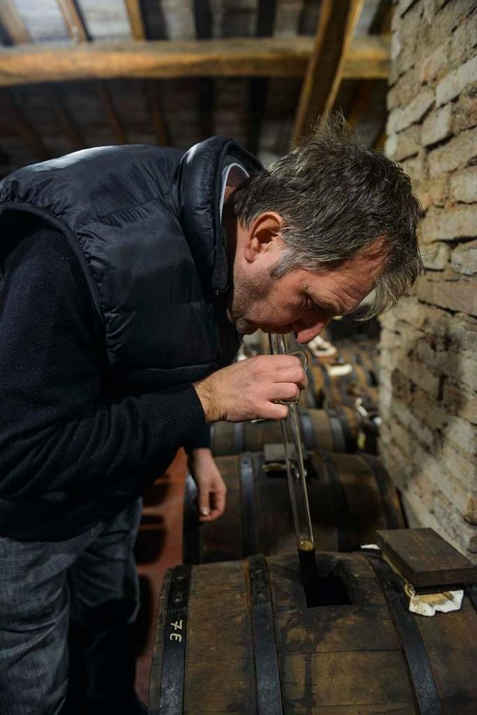 Balsamico-produsenten Guido med smakerør ned i et av fatene