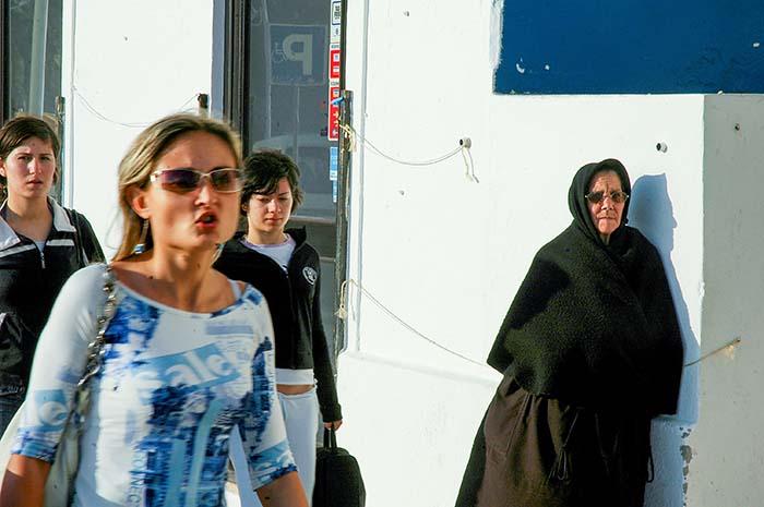 Ung kvinne passerer en svartkledd kone i Portugal