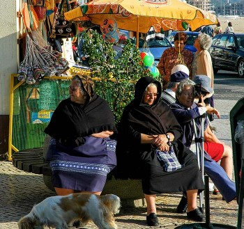 to gamle svartkledde damer utenfor en butikk i Nazaré