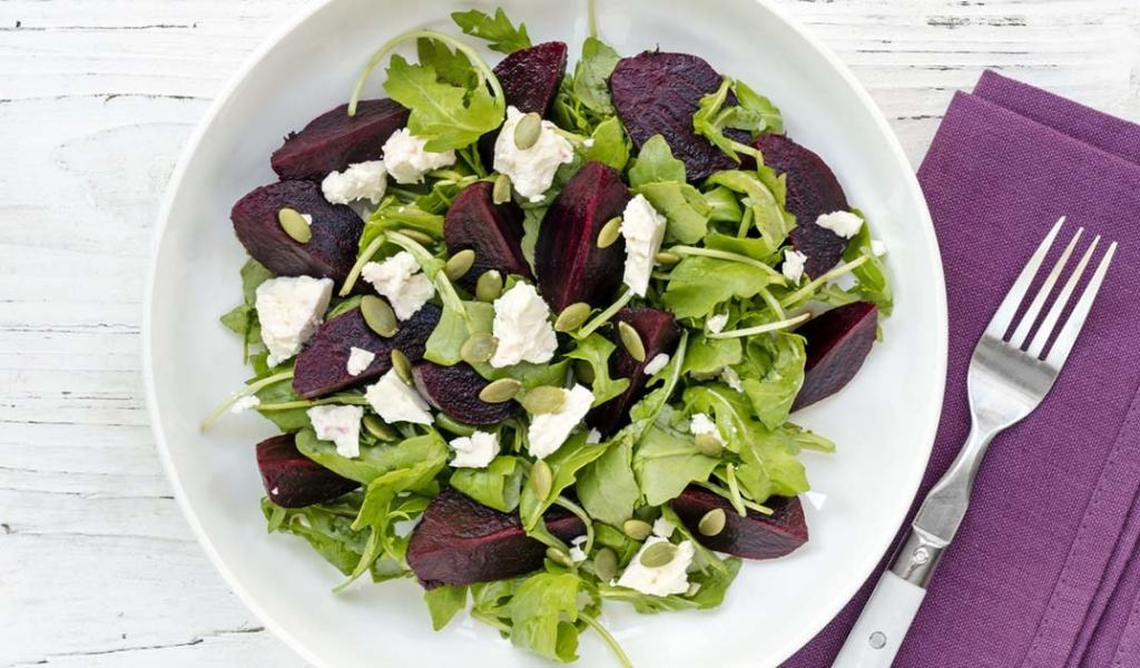 St. Supéry Warm Beet Salad with Greens and Pistachios in white bowl