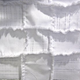 quilted tiles of fabric with threads removed and fringe
